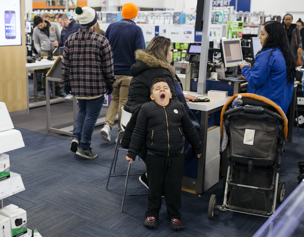 SOUTH PORTLAND, ME - NOVEMBER 24: Yousef, 5, lets out a yawn as he waits for his mother to finish shopping at Best Buy in the Maine Mall just after midnight on Black Friday. (Staff photo by Brianna Soukup/Staff Photographer)