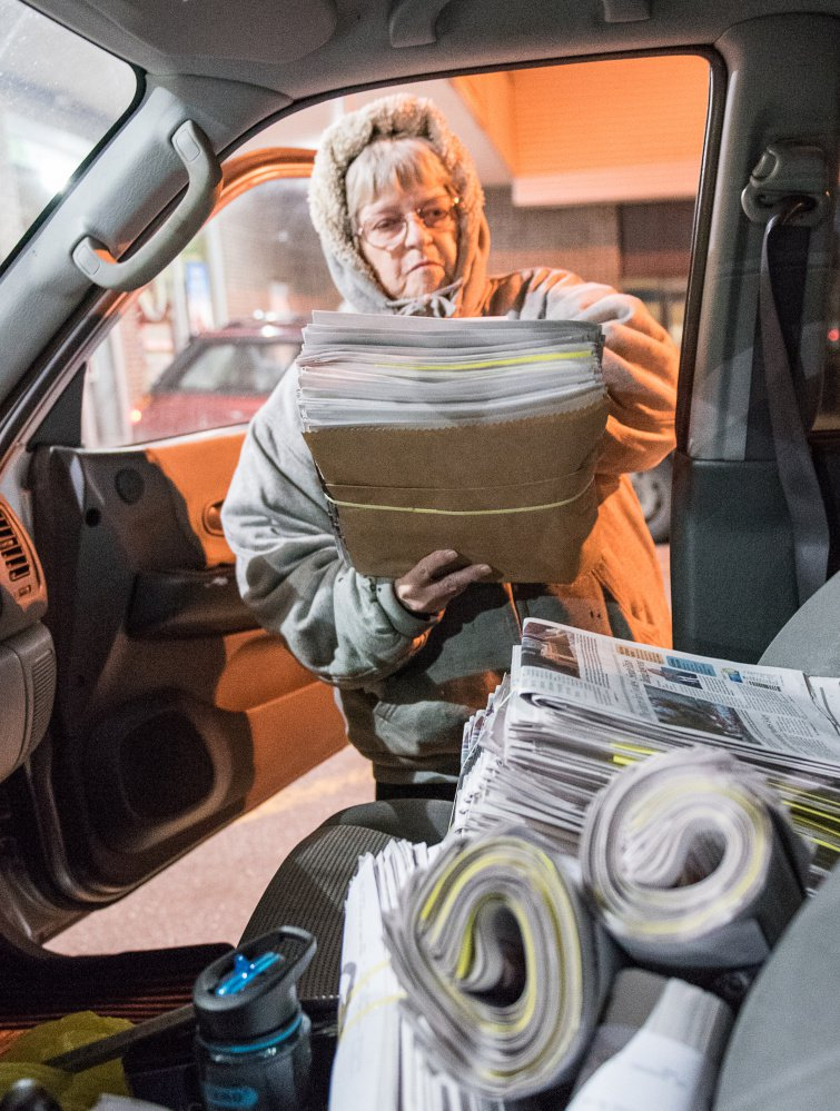 """Kay Brackley loads bundles of newspapers she picked up in Farmington on a Saturday. """"You do it night after night and you know what lights are on at houses and what cars are in the yard,"""" she said. """"You get to know your customers."""""""