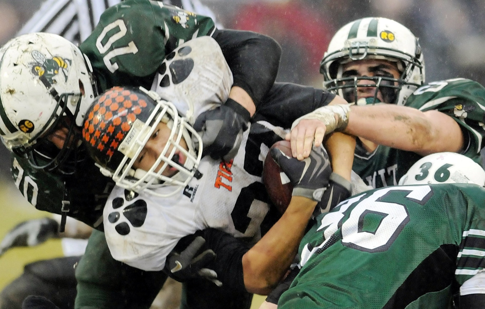Staff file photo by Andy Molloy   Gardiner running back Alonzo Connor tries to squeeze through three Leavitt defenders during the 2009 Pine Tree Conference Class B championship game in Turner.