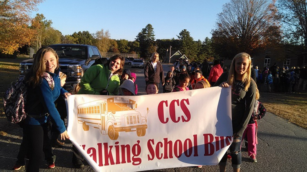Charlee Davis, left, and Breanna Rainville, right, hold Carrabec Community School's sign prior to its October Walking School Bus event.