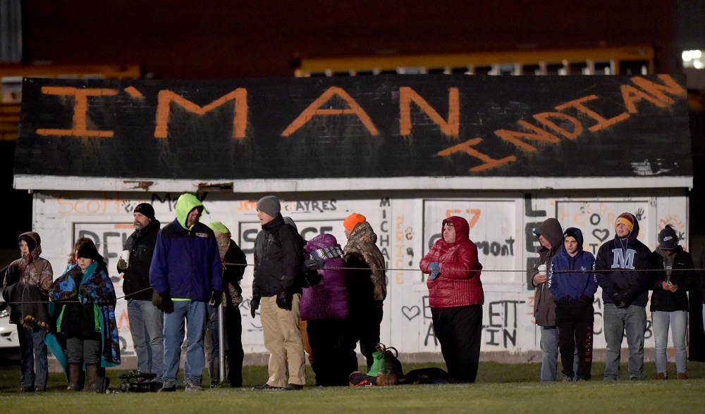 """Fans stand along the sideline of the Skowhegan Area High School football game against Lawrence High School on Friday in Skowhegan. A group of local professionals is expected to deliver a letter to the School Administrative District 54 board this evening to call for discontinuing the use of the term """"Indians"""" for the school's sports teams."""