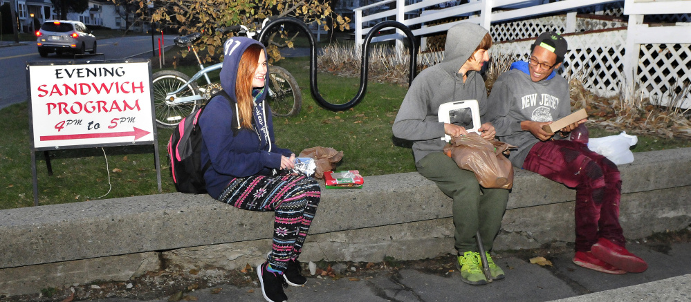 Three young recipients of the Universalist Unitarian Church Evening Sandwich program eat a meal outside the church in Waterville on Tuesday. From left are Montana Gulasky, Gradyn Dyer and Maliek Kirby-Milkins.