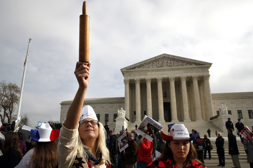 A demonstrator outside the U.S. Supreme Court in December 2017 holds up a rolling pin in support of baker Jack Phillips during arguments in the case of Masterpiece Cakeshop vs. Colorado Civil Rights Commission, also known as the wedding cake case.