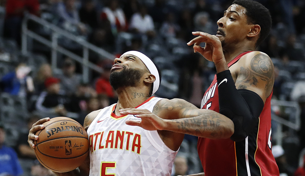 Atlanta's Malcolm Delaney, left, moves to the hoop while being guarded by Miami's Jordan Mickey in the Hawks' 110-104 win Monday in Atlanta.