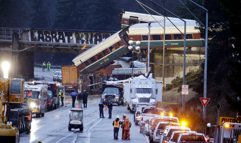 Lights illuminate cars from an Amtrak train that derailed above Interstate 5, Monday, Dec. 18, 2017, in DuPont, Wash. The Amtrak train making the first-ever run along a faster new route hurtled off the overpass Monday near Tacoma and spilled some of its cars onto the highway below, killing several people, authorities said. (AP Photo/Elaine Thompson)