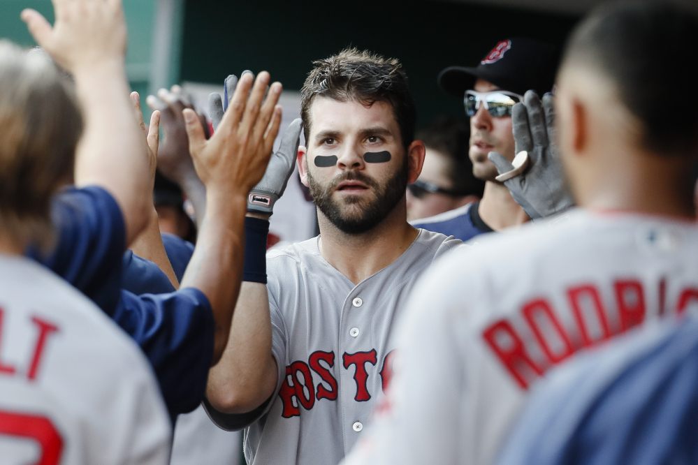 Boston Red Sox first baseman Mitch Moreland celebrates in the dugout after hitting a three-run home run off Cincinnati Reds starting pitcher Robert Stephenson in the sixth inning of a Sept. 23 game in Cincinnati.