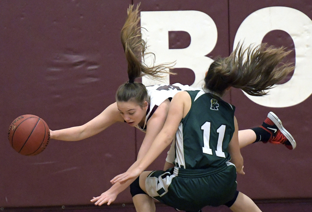 Richmond's Ashely Abbott goes over the top of Winthrop's Jillian Schmelzer during a Class C South game Wednesday in Richmond.