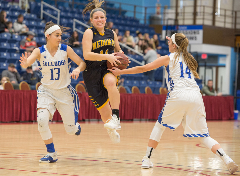 Medomak's Hallie Kunesh, center, feels the pressure from Madison's Emily Edgerly (13) and Sydney LeBlanc (14) at the Gold Rush Invitational Tournament on Wednesday at the Augusta Civic Center.