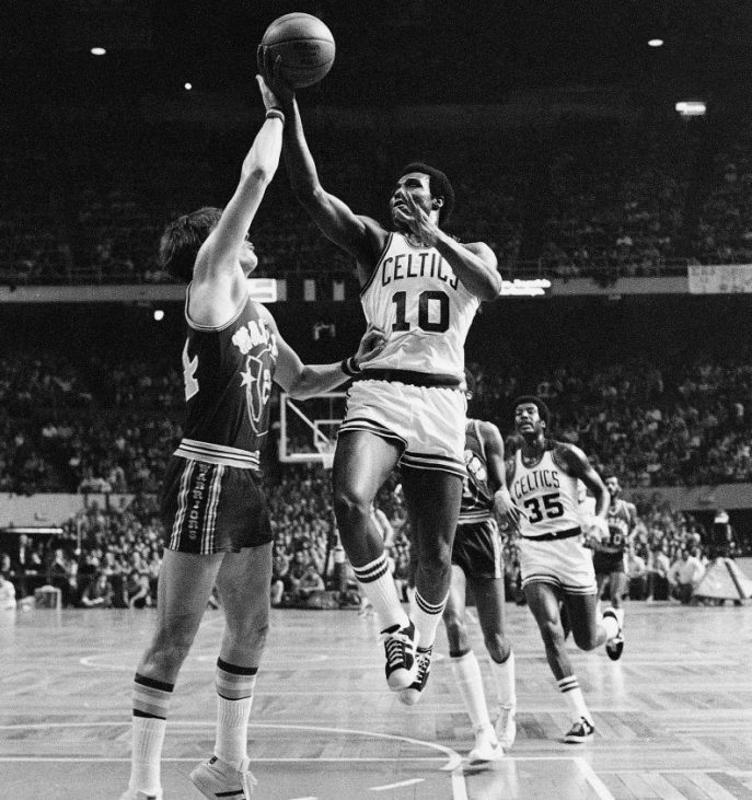 Jo Jo White of the Boston Celtics lays up a shot over Golden State's Rick Barry on Feb. 29, 1976. The Celtics went on to win the NBA Finals that season. White, who played a key role for the Celtics in that series, died on Tuesday at age 71 after a battle with cancer.