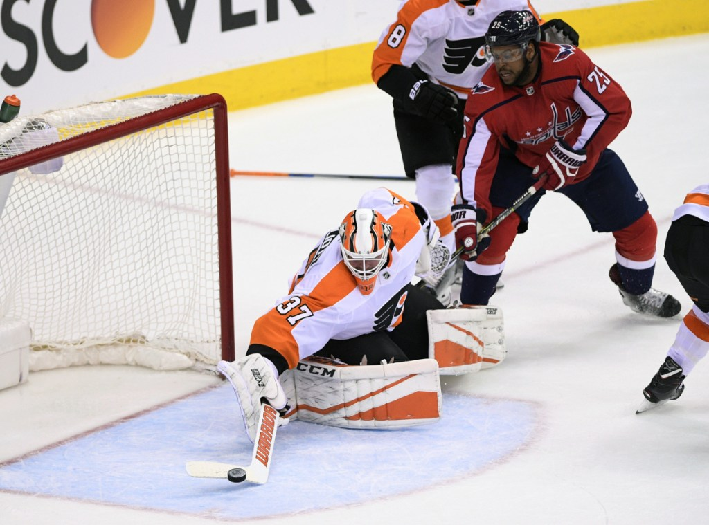 Flyers goaltender Brian Elliott reaches for the puck as Devante Smith-Pelly of the Capitals looks for a rebound Sunday during Philadelphia's 2-1 win in overtime.