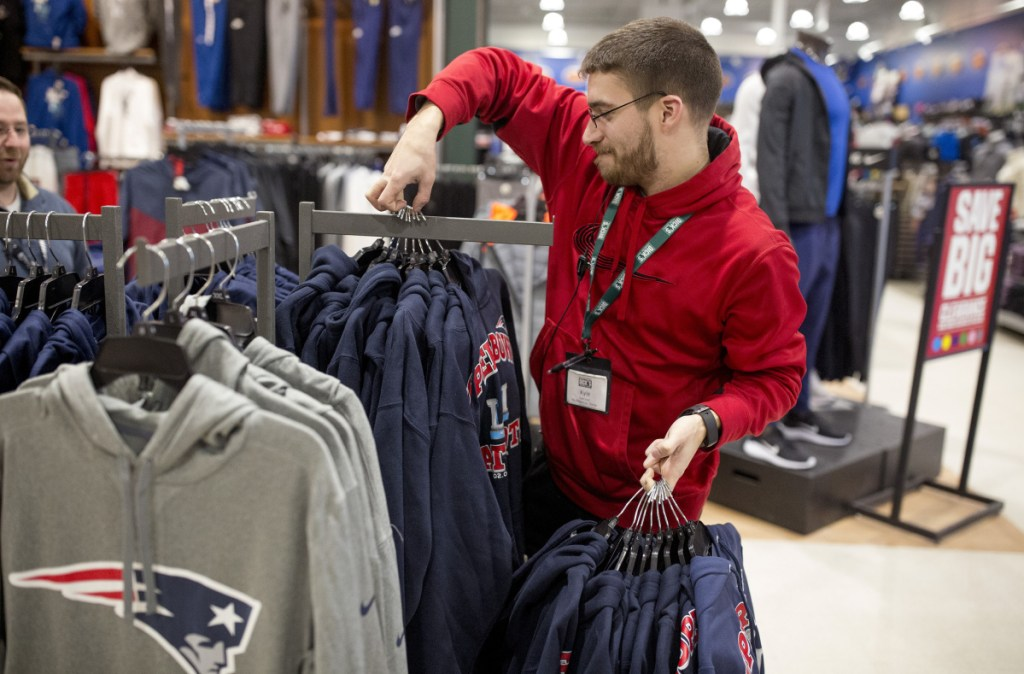 Kyle Jandreau puts out new Patriots merchandise at South Portland Dick's Sporting Goods. The store opened at 6 a.m. Monday.