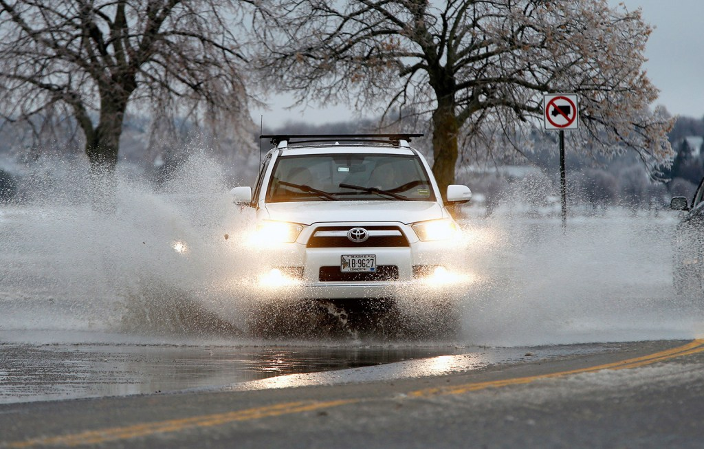 An SUV plows through a deep puddle at the intersection of Preble Street and Baxter Boulevard in Portland on Tuesday afternoon. A wintry mix of precipitation caused minor flooding on roads as slush blocked storm grates.