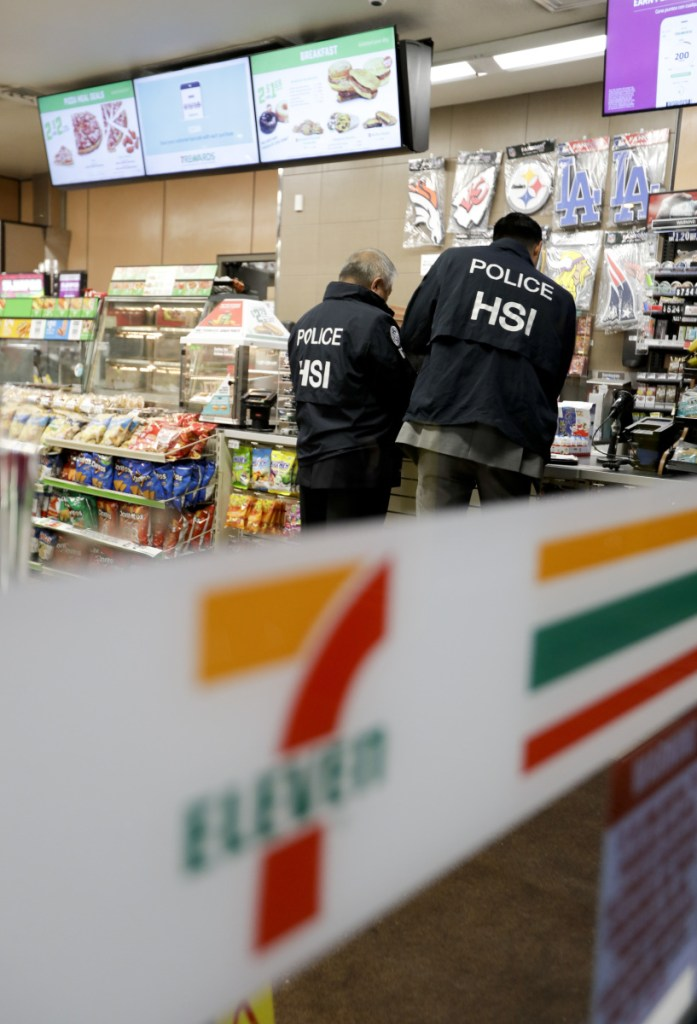 U.S. Immigration and Customs Enforcement agents serve an employment audit notice Wednesday at a 7-Eleven convenience store in Los Angeles. Agents said they targeted about 100 7-Eleven stores nationwide Wednesday to open employment audits and interview workers.