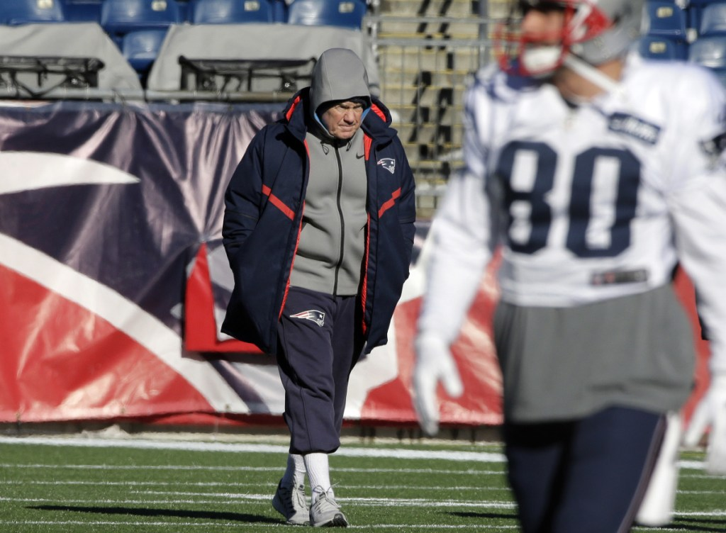 Patriots head coach Bill Belichick, center, walks on the field as wide receiver Danny Amendola warms up during practice Wednesday at Gillette Stadium.