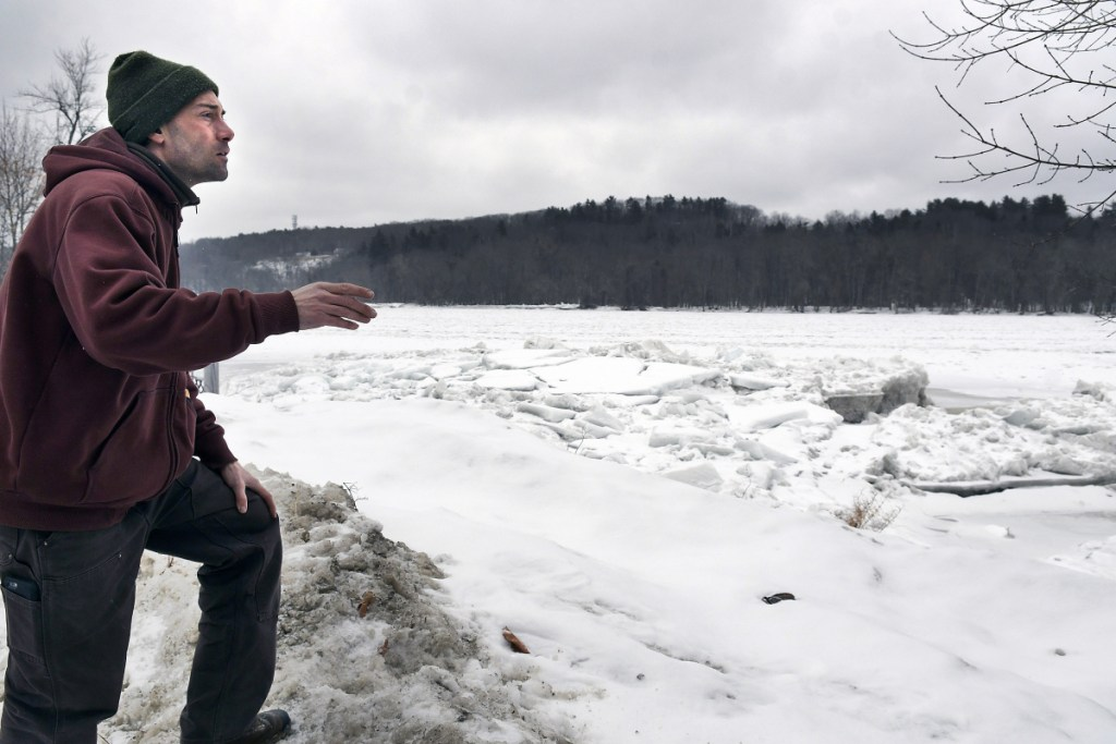 Nate Taczli surveys ice on the Kennebec River on Monday behind the Hallowell firm he manages, S. Masciadri & Sons. Forecasts call for rain and warmer temperatures on Tuesday, increasing the risks of flooding. The monument business has carved monuments and headstones at the same spot since 1918.