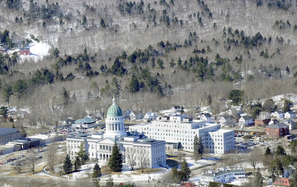 """Howard Hill, a 164-acre wood tract of land seen here on March 27, 2014, serves as the scenic forested backdrop for the Maine's State House in Augusta. A new plan for the land envisions a """"historical forest park"""" with several miles of recreational trails and a picnic area. The plan calls for cutting down some trees to create expansive scenic views of the state Capitol and areas east of the Kennebec River from high vantage points."""