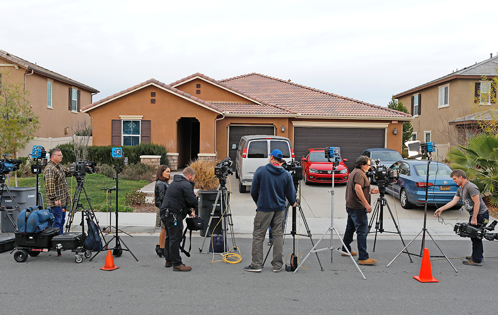 Members of the news media stand outside the home of David Allen Turpin and Louise Ann Turpin in Perris, California, Monday.