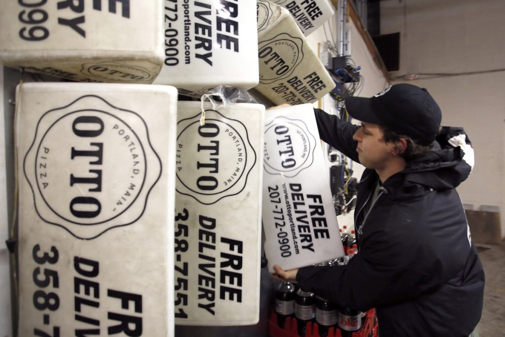 Nick Folan, a cook and fill-in delivery driver for Otto Pizza, pulls a magnetic sign from the wall of the franchise's location in South Portland.