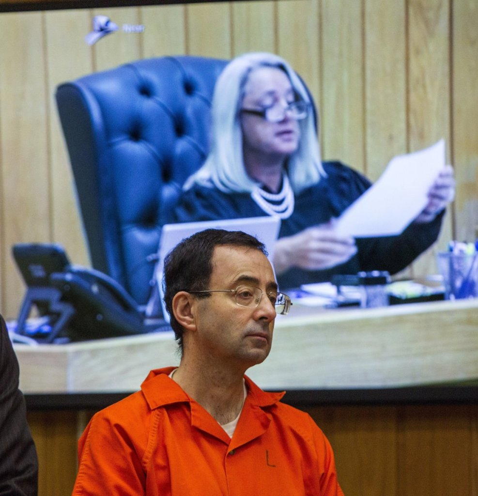 Larry Nassar listens Monday as Judge Janice Cunningham (pictured on the monitor) sentences him to 40 to 125 years for molesting young athletes at an elite Michigan gymnastics club.