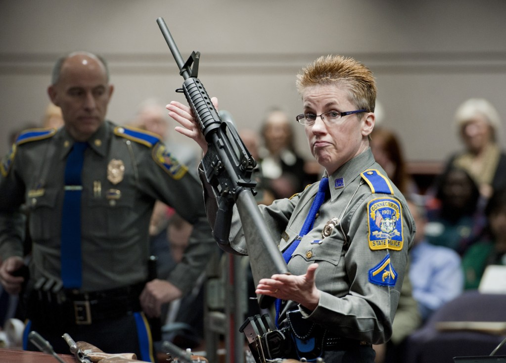 Firearms training unit Detective Barbara J. Mattson, of the Connecticut State Police, holds up a Bushmaster AR-15 rifle, the same make and model of gun used by Adam Lanza in the Sandy Hook School shooting, during a hearing of a legislative subcommittee in Hartford, Conn. Remington, the gunmaker beset by falling sales and lawsuits tied to the Sandy Hook Elementary School massacre, said Monday that it has reached a financing deal that would allow it to continue operating as it files for Chapter 11 bankruptcy protection.