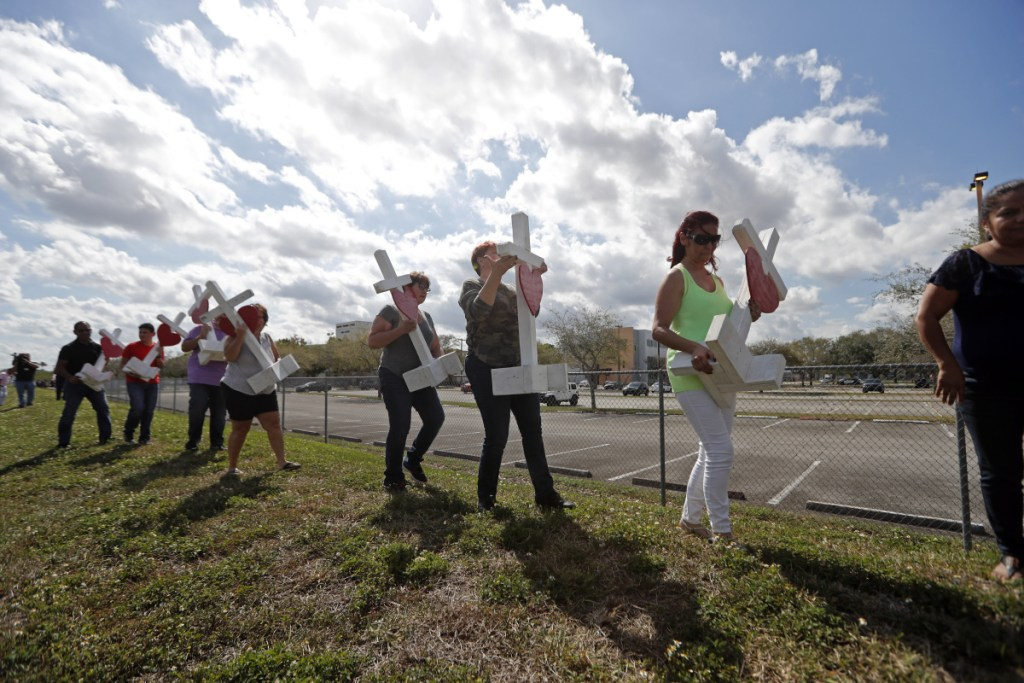 Volunteers carry 17 crosses to be placed outside the Marjory Stoneman Douglas High School in Parkland, Fla., where 17 people were killed in a mass shooting.
