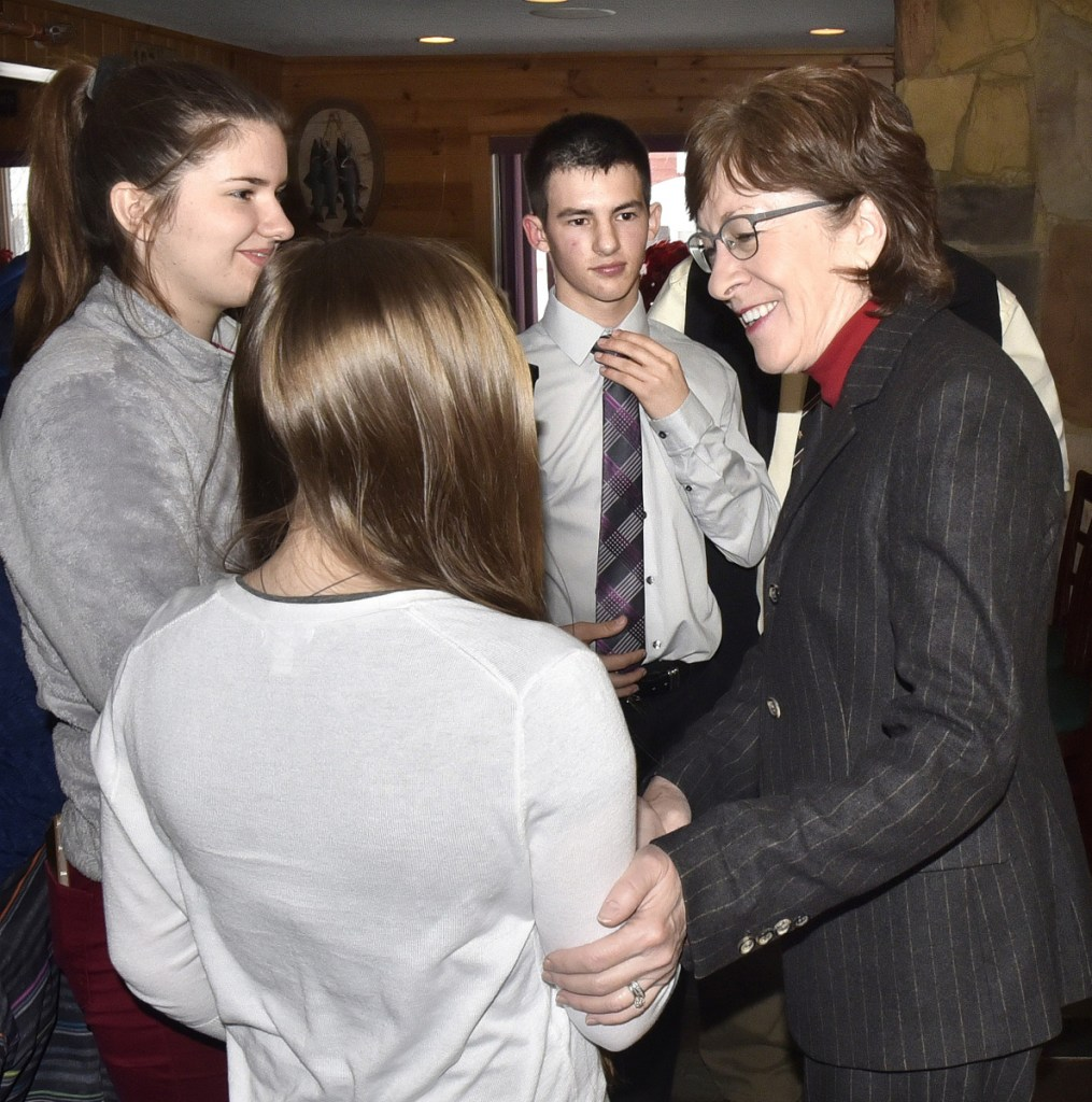 U.S. Sen. Susan Collins greets Forest Hills Consolidated School students Thursday during a stop at Schmoose's Bar and Grill in Jackman. From left are Alexandra Lessard, Demitria Giroux and Carson Veilleux, who were chosen to represent the school for the event. Collins came to show her support for Jackman residents, whose town received negative publicity after the former town manager publicly expressed his racist views.
