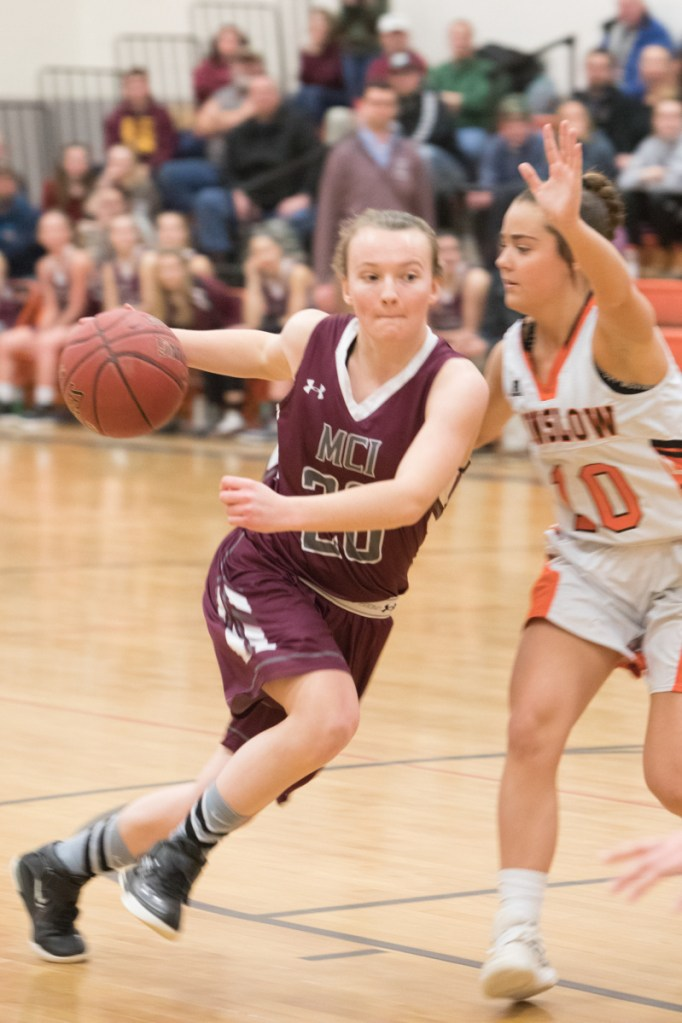 Photo by Jennifer Bechard   MCI's Sydney Morton, left, goes in for a layup while Winslow's Sarah Guimond defends during a Class B North game Thursday night in Winslow.