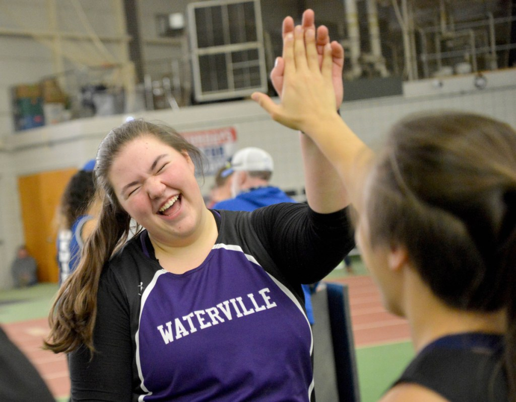 Waterville junior Sarah Cox, center, highs-fives teammate Jennasea Hubbard after winning the shot put with a throw of 35-3.5 at a Kennebec Valley Athletic Conference track and field meet on Feb. 3 at Bowdoin College in Brunswick.