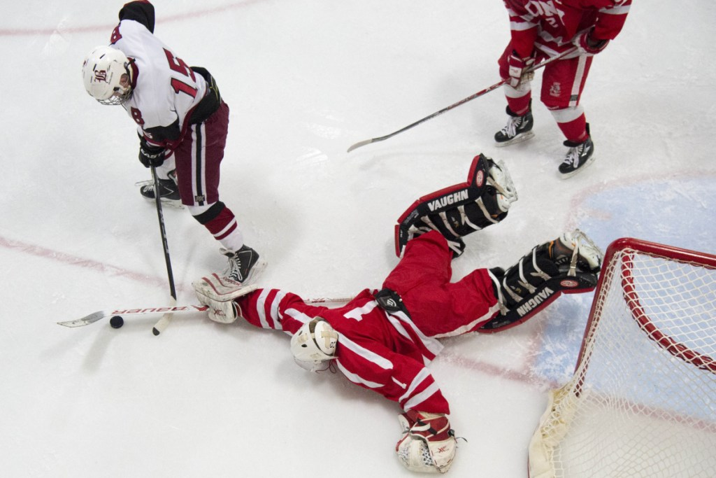 Cony goalie Dalton Bowie (1) makes a save as Bangor's Alex Inman (15) looks for the rebound score Tuesday at Sawyer Arena in Bangor.