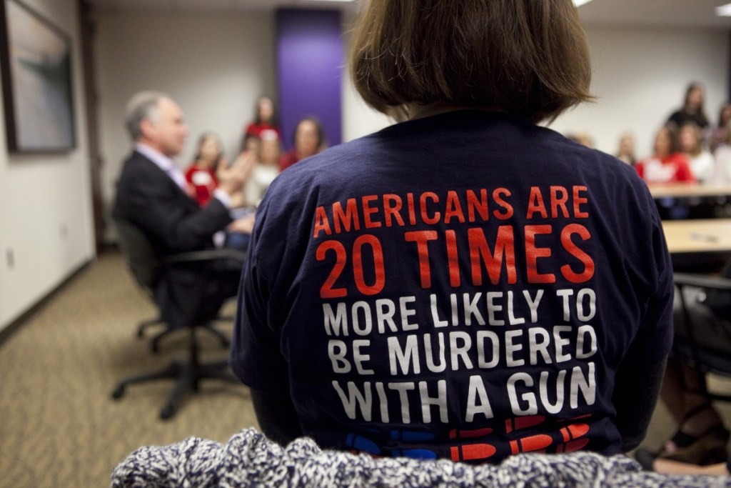 Orna Malone, wearing an anti-gun shirt, listens last week as Sen. Tim Kaine, D-Va., speaks to Moms Demand Action, a group advocating for more gun control, in Richmond, Virginia. The debate over guns has spread across the country since last month's shooting in Parkland, Fla., but many key lawmakers in Congress are choosing to remain silent.