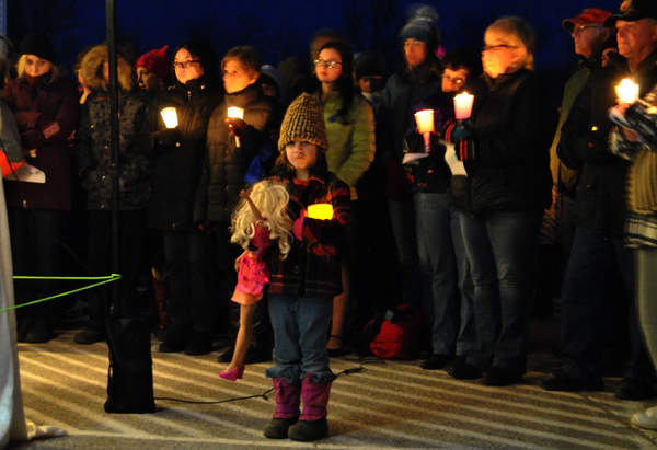 A girl carries a doll during a candlelight vigil Sunday night for 10-year-old Marissa Kennedy in Stockton Springs. Marissa's parents are accused of beating her to death.