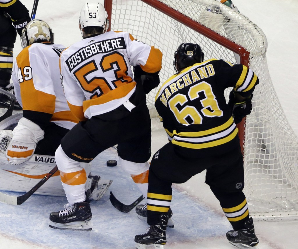 Brad Marchand reaches behind Flyers goalie Alex Lyon and Shayne Gostisbehere for the winning goal in Boston's 3-2 victory.