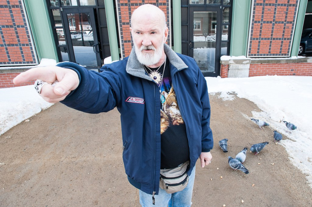 David Sites points to Oak Park Apartments in Lewiston, where he lives, as birds feed on bread he has just thrown down for them. Despite a threat of eviction for feeding the birds, Sites plans to continue feeding the pigeons, as he has done for the past 10 years. Visit sunjournal.com to watch a video of Sites feeding the birds and explaining why he plans to continue.