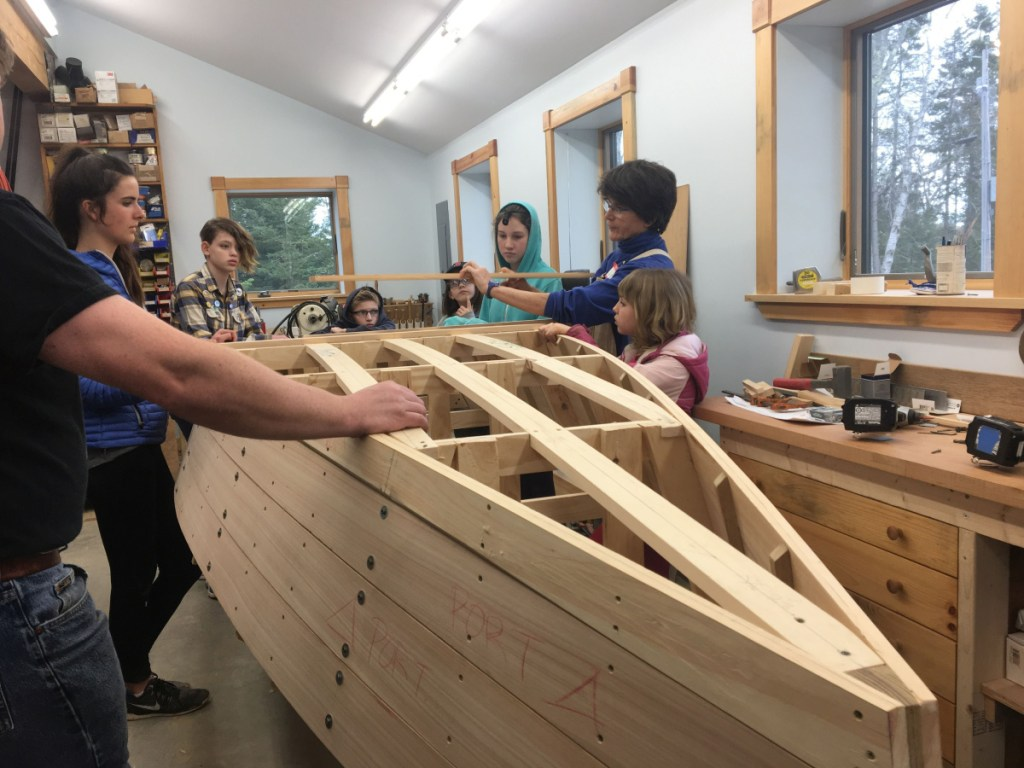 """Cundy's Harbor resident Ann Flannery works with the """"Harpswell Boat Builders,"""" a free program she created for local kids ages 6 and older. When the rowboat is complete, it will be auctioned off to benefit the Holbrook Community Foundation."""