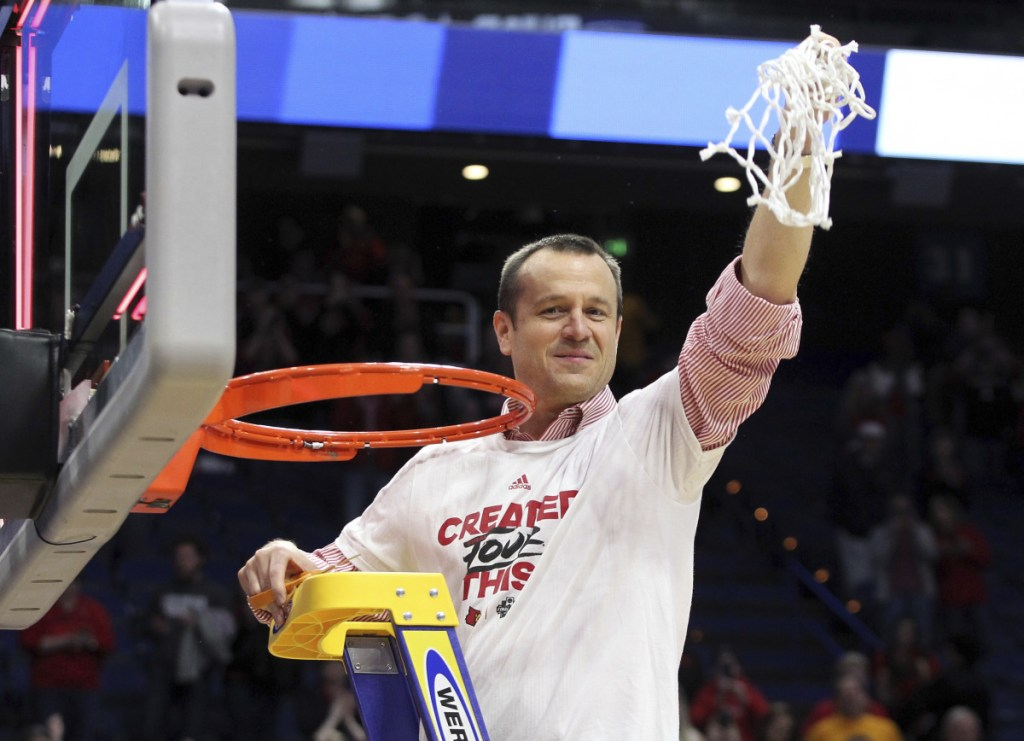 Louisville Coach Jeff Walz holds up the net after his team beat Oregon State 76-43 on Sunday in Lexington, Kentucky, to advance to the Final Four.