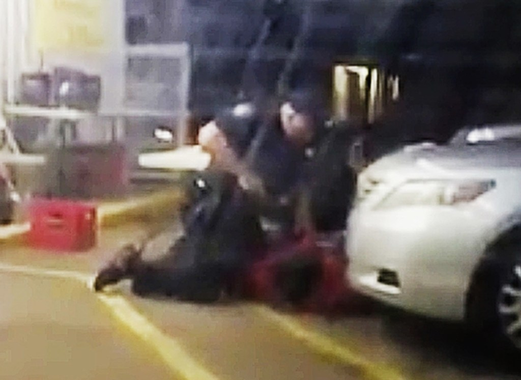 In this image made from video provided by Arthur Reed, Alton Sterling is restrained by two police officers outside a convenience store in Baton Rouge, La., on July 5, 2016. Moments later, one of the officers shot and killed Sterling.