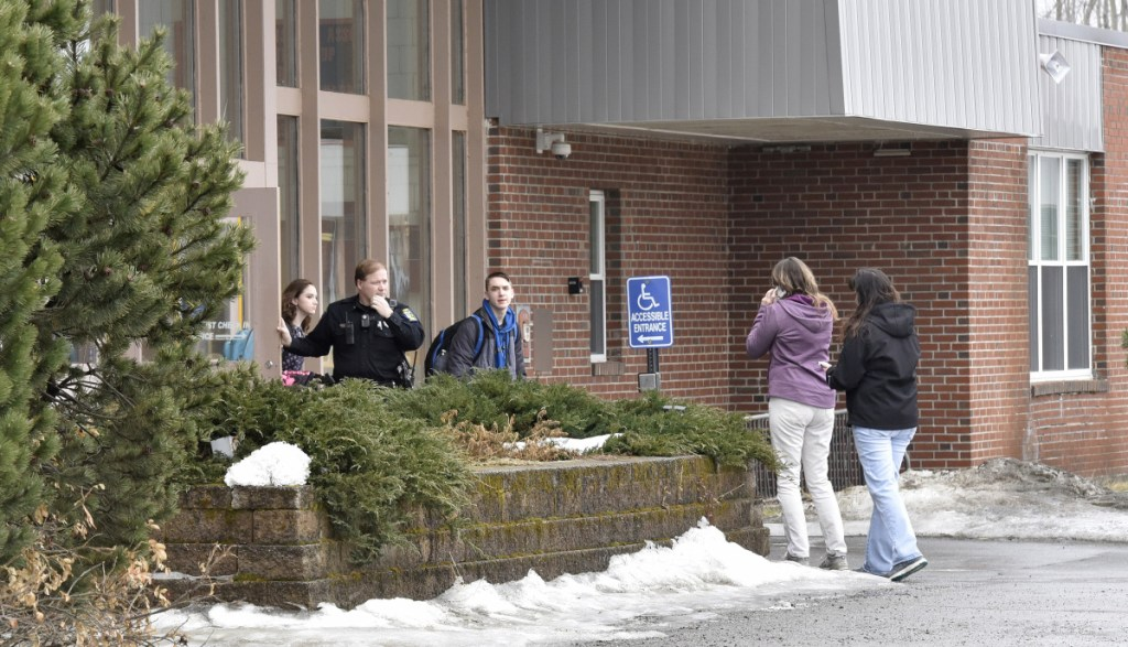 SAD 54 School Resource Officer David Daigneault speaks with parents as students exit the Skowhegan Area High School during a lockout after a threat made Thursday. It was the second threat there this week. Students were allowed to leave the school but no one could enter.