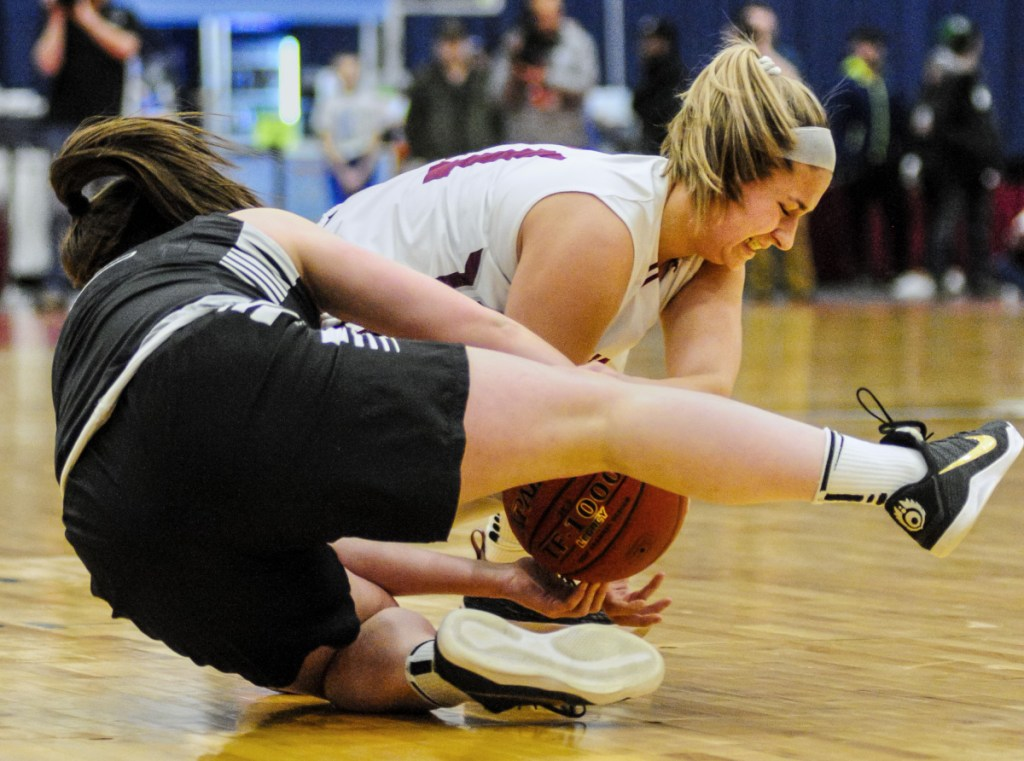 Staff photo by Joe Phelan Houlton's Abbie Worthley, left, and Monmouth's Hannah Anderson wrestle for a loose ball in the Class C state championship game Saturday at the Augusta Civic Center.