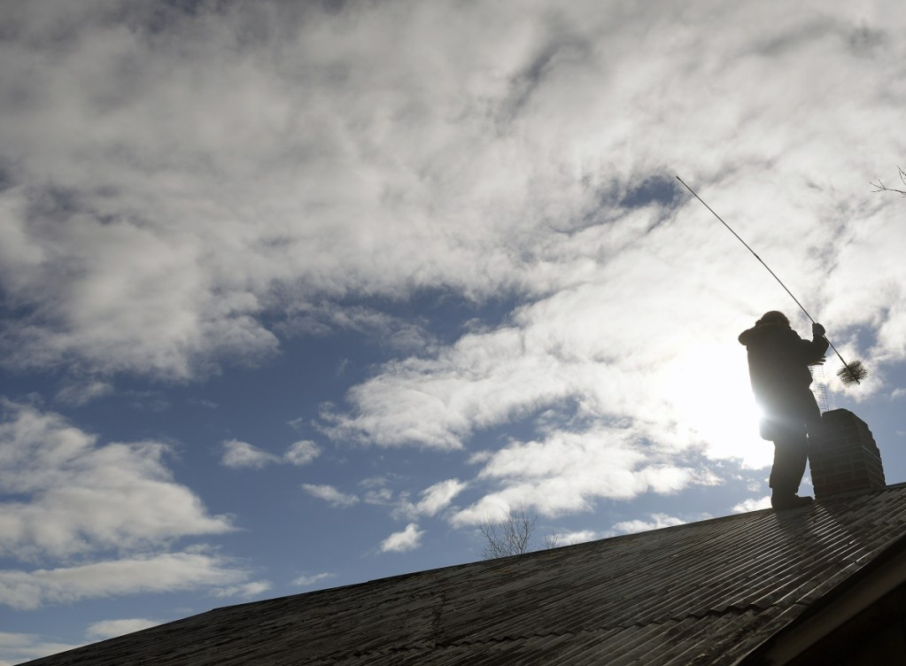 Marion Messenger sweeps the chimney on her home Tuesday in Wayne. Messenger said she likes to give the primary source of heat a brush every three weeks to keep slow-burning fires from creating much creosote. She climbed up there to get ahead of the snowstorm in the forecast for Wednesday night into Thursday.