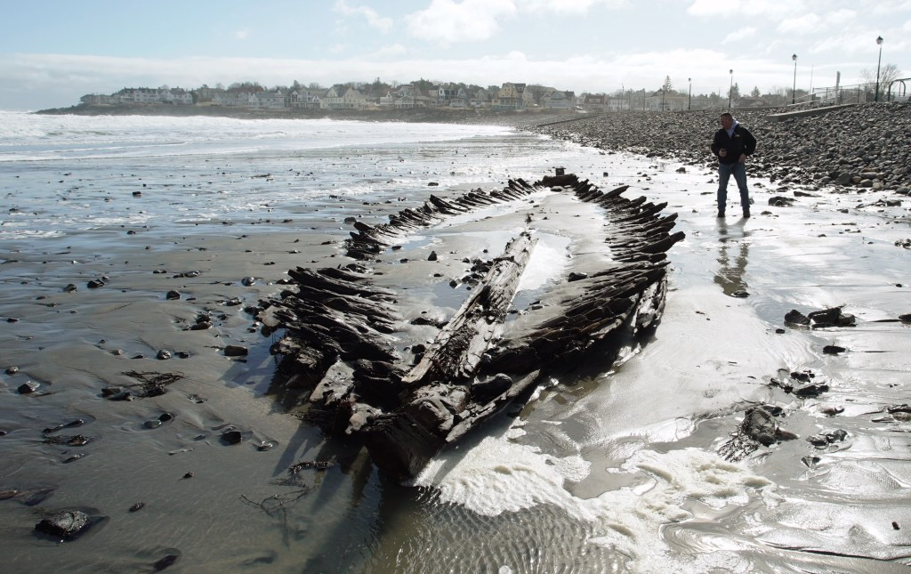 Dan DeButts of Lebanon checks out the shipwreck at Short Sands Beach in York on Monday. The shipwreck was uncovered over the past three days of coastal flooding. The last time it was revealed was in 2013.