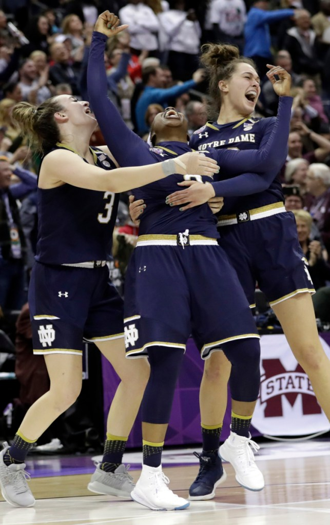 Notre Dame's Arike Ogunbowale, center, celebrates with teammates Marina Mabrey, left, and Kathryn Westbeld after her last-second 3-pointer Sunday gave the Irish their second national title.