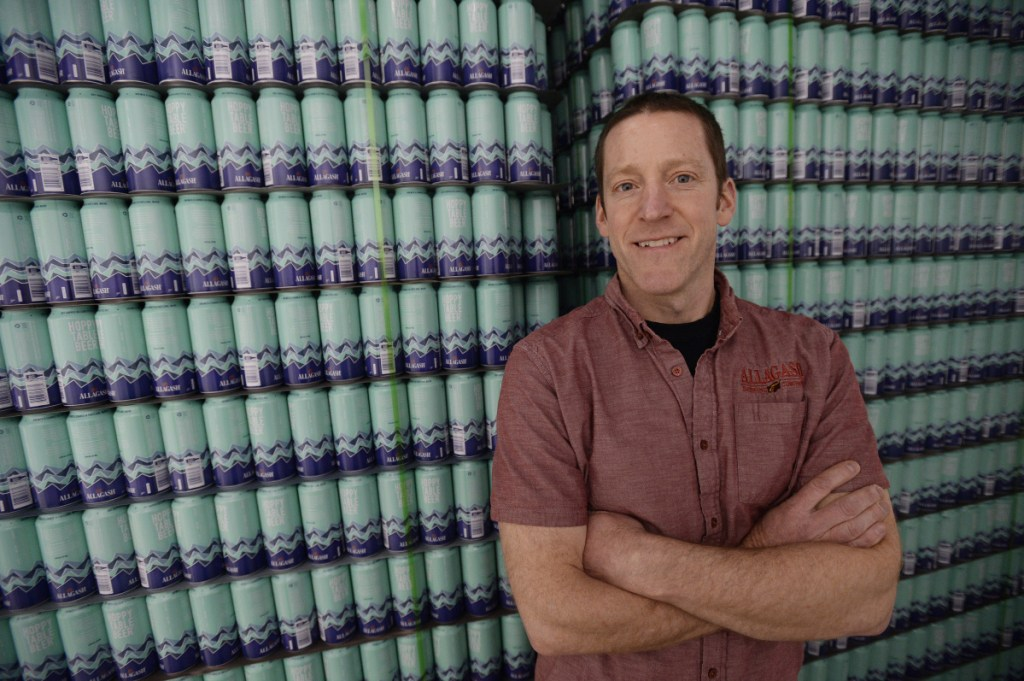 "Allagash brewmaster Jason Perkins stands near a stack of 16-ounce cans that will soon be filled with Hoppy Table Beer as the Portland company – and Maine's largest brewery – tests out a container other than bottles. Canning is ""something we're excited to learn more about,"" he said. Now just two of the state's 10 largest breweries sell their beer only in a bottle."