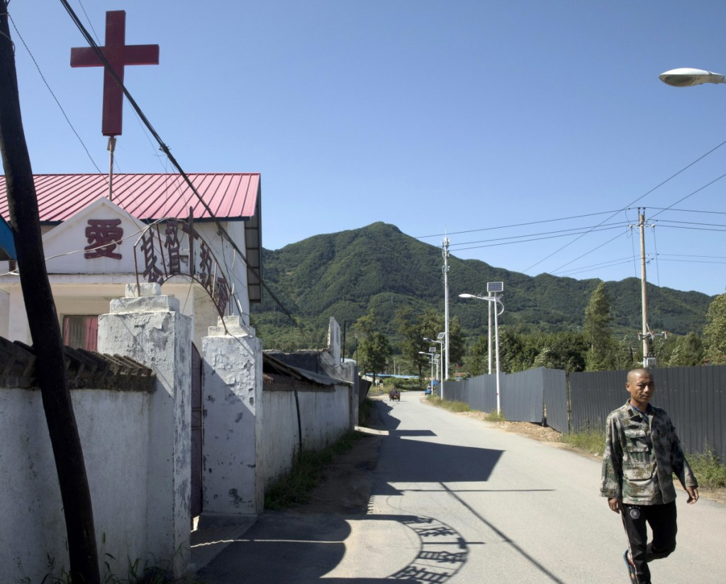 A cross on a church beckons believers in a border town in northeastern China's Jilin province, where the risks are high for missionaries offering prayer and guidance to North Koreans passing by. It is dangerous work for all parties and a South Korean pastor says at least 10 front-line church people have died mysteriously in recent years. At left, the Rev. Kim Kyou Ho, head of the Chosen People Network, shows a portrait of one of them, the Rev. Han Chung-ryeol, found dead in 2016. Associated Press/Ng Han Guan/Ahn Young-joon