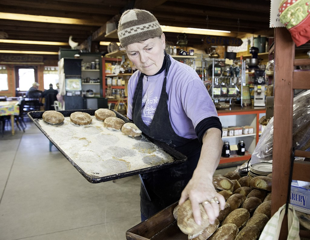 """Gloria Varney puts out fresh-baked dinner rolls at Nezinscot Farm in Turner. Varney offers what she calls a """"Full Diet CSA,"""" a program in which members buy shares that are treated as credits that customers can spend on anything, including organic vegetables, eggs, baked goods and meals at the farm cafe."""