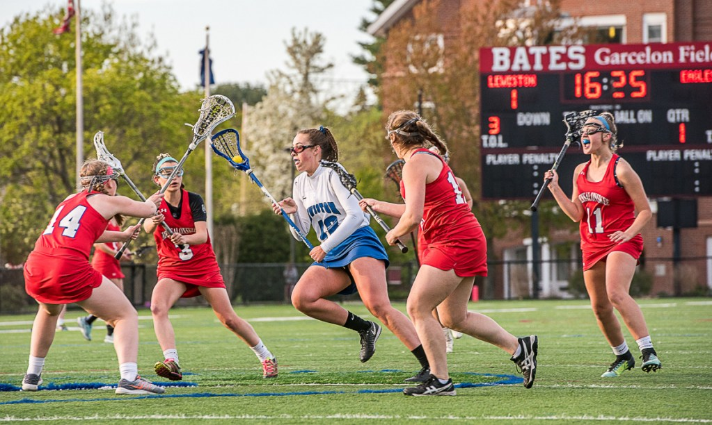 Lewiston's Grace Dumond drives through a sea of Messalonskee players during Wednesday night's lacrosse game at Bates College in Lewiston. From the left are Katie Luce, Chloe Tilley, Emily Crowell and Shauna Clark.
