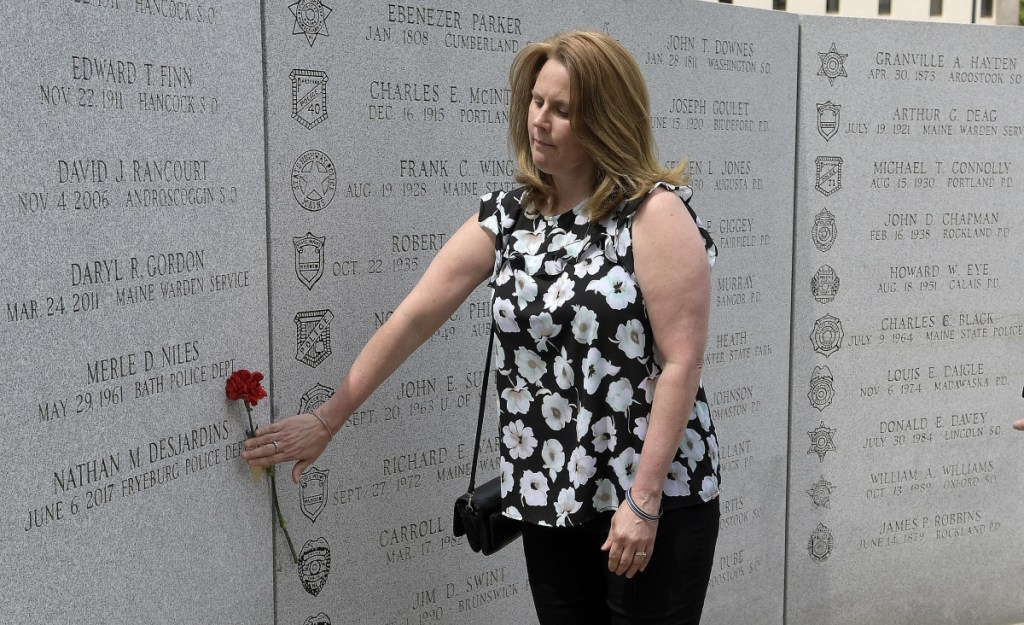 Nicole Desjardins places a carnation next to the name of her son, Nathan Desjardins, of the Fryeburg Police Department, at the Maine Law Enforcement Officer's Memorial in Augusta on Thursday. Desjardins, who died during a water rescue in 2017, was the 85th name to be added to Memorial.