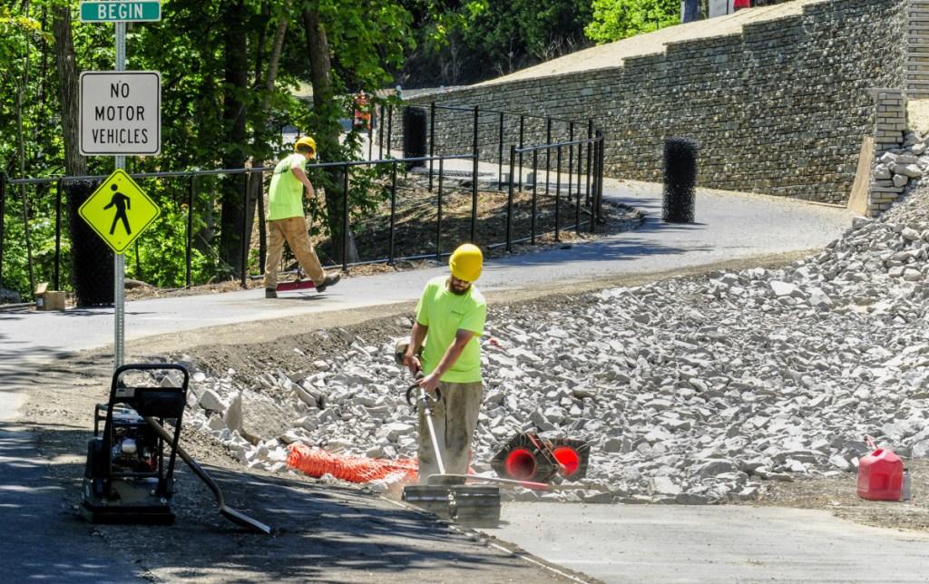 Josh Billings, left, and John Smith Cross Excavation, sweep the newest section of the Kennebec River Rail Trail on Tuesday in Augusta. The last quarter-mile of the trail leading from Augusta Waterfront park on Front Street to the base of Memorial Bridge will be officially opened with a ceremonial ribbon cutting at noon on Wednesday.