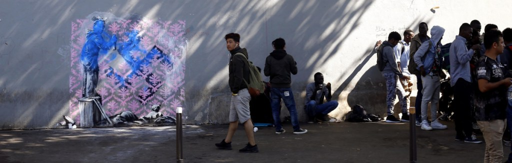 Graffiti attributed to street artist Banksy appears on a wall near a group of Paris migrants. It depicts a child, standing on an object at left, spray-painting wallpaper over a swastika.
