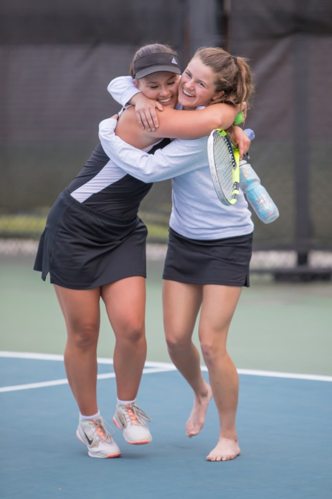 Photo by Jennifer Bechard   Maranacook singles players Emma Wadsworth, left, and Madelyn Dwyer embrace after the the Black Bears sank Carrabec to win the Class C South championship Thursday afternoon at Bates College in Lewiston.