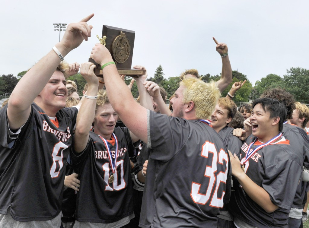 Portland Press Herald photo by John Ewing   Brunswick co-captain Max Gramins holds aloft the Class B boys lacrosse state championship plaque after the Dragons sank Greely in overtime Saturday in Portland.